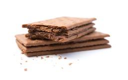 Μπισκότα σάντουιτς γεύσης σοκολάτας με τα δαγκώματα στο λευκό στοκ εικόνα