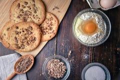 Μπισκότα σοκολάτας στον ξύλινο πίνακα με τα αυγά και τα συστατικά αλευριού Στοκ φωτογραφίες με δικαίωμα ελεύθερης χρήσης