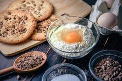 Μπισκότα σοκολάτας στον ξύλινο πίνακα με τα αυγά και τα συστατικά αλευριού Στοκ Εικόνες