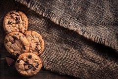 Μπισκότα σοκολάτας στη σκοτεινή πετσέτα στον ξύλινο πίνακα Chi σοκολάτας Στοκ φωτογραφία με δικαίωμα ελεύθερης χρήσης