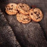 Μπισκότα σοκολάτας στη σκοτεινή πετσέτα στον ξύλινο πίνακα Chi σοκολάτας Στοκ Φωτογραφίες