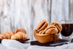 Μπισκότα στα ξύλινα πιάτα με τον καφέ σε ένα ελαφρύ υπόβαθρο Στοκ Φωτογραφία