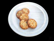Μπισκότα στο άσπρο πιάτο που απομονώνεται στο μαύρο υπόβαθρο στοκ φωτογραφίες