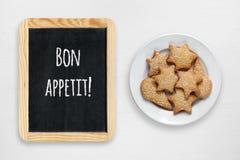 Μπισκότα στο πιάτο και το μικρό πίνακα με τις επιθυμίες Bon appetit Στοκ εικόνα με δικαίωμα ελεύθερης χρήσης