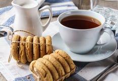 Μπισκότα τσιπ, ένα φλυτζάνι του τσαγιού, ζάχαρη, γάλα, ποτήρι του νερού πάγου Στοκ εικόνα με δικαίωμα ελεύθερης χρήσης