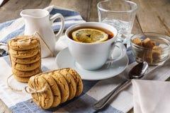 Μπισκότα τσιπ, ένα φλυτζάνι του τσαγιού με το λεμόνι, ζάχαρη, γάλα, γυαλί του ολοκληρωμένου κυκλώματος Στοκ Εικόνες