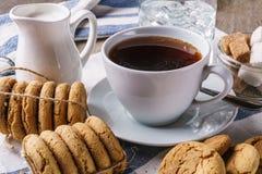 Μπισκότα τσιπ, ένα φλυτζάνι του τσαγιού με το λεμόνι, ζάχαρη, γυαλί του πάγου wate Στοκ Φωτογραφίες