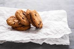 Μπισκότα τσιπ σοκολάτας με μια φέτα της σοκολάτας, σε ένα κομμάτι του χαρτί ψησίματος, με το διάστημα αντιγράφων στοκ φωτογραφίες