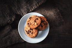 Μπισκότα τσιπ σοκολάτας με τα κομμάτια σοκολάτας στο άσπρο σκοτάδι πιάτων Στοκ φωτογραφία με δικαίωμα ελεύθερης χρήσης