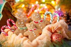 Μπισκότα υπό μορφή μικρών ατόμων για τα Χριστούγεννα σε ένα υπόβαθρο μιας γιρλάντας και ένα κιβώτιο υπό μορφή χριστουγεννιάτικου  Στοκ εικόνα με δικαίωμα ελεύθερης χρήσης
