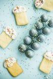 Μπισκότα υπό μορφή pasque και μπλε-χρωματισμένων αυγών 2 όλα τα αυγά Πάσχας έννοιας νεοσσών κάδων ανθίζουν τη χλόη χρωμάτισαν τις Στοκ Φωτογραφία