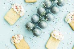 Μπισκότα υπό μορφή pasque και μπλε-χρωματισμένων αυγών 2 όλα τα αυγά Πάσχας έννοιας νεοσσών κάδων ανθίζουν τη χλόη χρωμάτισαν τις Στοκ Εικόνα
