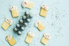 Μπισκότα υπό μορφή pasque και μπλε-χρωματισμένων αυγών 2 όλα τα αυγά Πάσχας έννοιας νεοσσών κάδων ανθίζουν τη χλόη χρωμάτισαν τις Στοκ Εικόνες