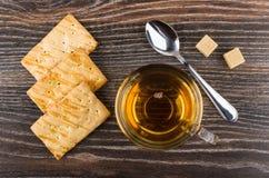 Μπισκότα, φλυτζάνι του τσαγιού, άμορφα ζάχαρη και κουταλάκι του γλυκού στον πίνακα Στοκ Φωτογραφία
