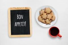 Μπισκότα, φλυτζάνι καφέ και μικρός πίνακας με τις επιθυμίες Bon appetit Στοκ εικόνες με δικαίωμα ελεύθερης χρήσης