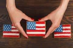 Μπισκότο με τα αμερικανικά πατριωτικά χρώματα στα χέρια Στοκ εικόνες με δικαίωμα ελεύθερης χρήσης