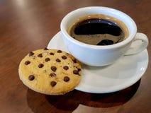 Μπισκότο τσιπ σοκολάτας που τίθεται στο πλαίσιο του μαύρου φλυτζανιού καφέ στοκ φωτογραφία με δικαίωμα ελεύθερης χρήσης