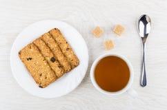 Μπισκότο-Muesli στο πιάτο, φλυτζάνι του τσαγιού, ζάχαρη, κουταλάκι του γλυκού Στοκ φωτογραφία με δικαίωμα ελεύθερης χρήσης