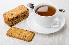 Μπισκότο-Muesli, φλυτζάνι του τσαγιού στο πιατάκι, κουταλάκι του γλυκού στον πίνακα Στοκ Εικόνες