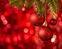 Μπιχλιμπίδια Χριστουγέννων στο κόκκινο υπόβαθρο με τα σπινθηρίσματα Στοκ Εικόνες