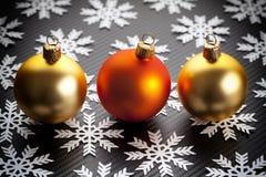 Μπιχλιμπίδια και snowflakes Χριστουγέννων στο μαύρο υπόβαθρο Στοκ εικόνες με δικαίωμα ελεύθερης χρήσης