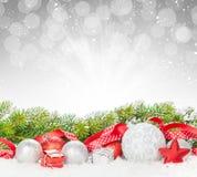 Μπιχλιμπίδια Χριστουγέννων και κόκκινη κορδέλλα με το δέντρο έλατου χιονιού Στοκ Εικόνες