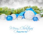 Μπιχλιμπίδια Χριστουγέννων και μπλε κορδέλλα με το δέντρο έλατου χιονιού Στοκ Εικόνες