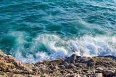 Μπλε άποψη της θάλασσας με ένα άσπρο κύμα, ψεκασμός σχετικά με το βράχο παραλιών Το κύμα χτυπά την ακτή Στοκ εικόνα με δικαίωμα ελεύθερης χρήσης