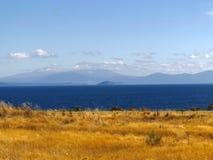 μπλε ήρεμη λίμνη Βουνά που καλύπτονται μπλε από τα σύννεφα Χρυσή ακτή Fied χλόης στοκ φωτογραφία