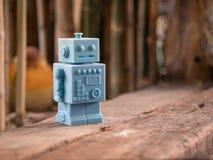 Μπλε αναδρομικά παιχνίδια ρομπότ και ξύλινο σχέδιο πατωμάτων στο φυσικό backgrou Στοκ Εικόνες