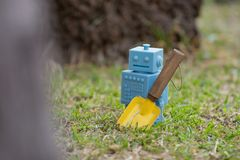 Μπλε αναδρομικά παιχνίδια ρομπότ με τα εργαλεία κήπων στα φυσικά πράσινα φύλλα Στοκ Εικόνες