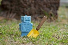Μπλε αναδρομικά παιχνίδια ρομπότ με τα εργαλεία κήπων στα φυσικά πράσινα φύλλα Στοκ φωτογραφία με δικαίωμα ελεύθερης χρήσης