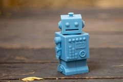 Μπλε αναδρομικά παιχνίδια ρομπότ στο ξύλινο σχέδιο πατωμάτων στο φυσικό backgroun Στοκ Εικόνες