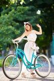 Μπλε αναδρομικό ποδήλατο κοντά στο όμορφο κορίτσι στο θερινό φως του ήλιου στοκ φωτογραφίες με δικαίωμα ελεύθερης χρήσης