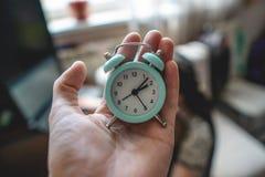 Μπλε αναλογικό ξυπνητήρι υπό εξέταση στο υπόβαθρο δωματίων Έννοια του χρόνου και αργά για την εργασία στοκ εικόνα