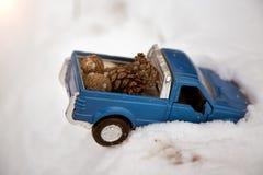 Μπλε ανοιχτό φορτηγό παιχνιδιών που κολλιέται snowdrift Φέρνοντας κώνοι έλατου στην πλάτη ενός σώματος αυτοκινήτων στοκ εικόνα με δικαίωμα ελεύθερης χρήσης
