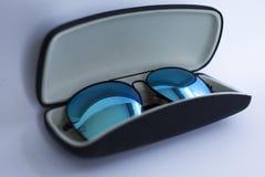 Μπλε αντανακλημένα γυαλιά ηλίου σε μια περίπτωση στοκ εικόνες