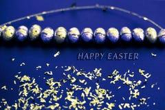 Μπλε βαμμένη ευχετήρια κάρτα Πάσχας Χρυσό κομφετί στα χρωματισμένα φύλλα Χρυσό αυγό Πάσχας στην επιφάνεια Τοπ άποψη των ρυθμίσεων στοκ εικόνες