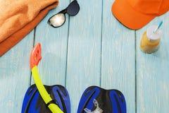 Μπλε βατραχοπέδιλα, γυαλιά ηλίου πετσετών και τ σε ένα ανοικτό μπλε υπόβαθρο μια ηλιόλουστη ημέρα στοκ φωτογραφίες