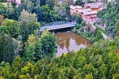 Μπλε γέφυρα μετάλλων πέρα από τον ποταμό Ohre στο χωριό Kyselka όταν αντιμετωπίζεται από την επιφυλακή πετρών πάνω από το λόφο Bu Στοκ Εικόνες
