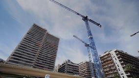 Μπλε γερανοί κατασκευής στο Μονακό στα πλαίσια των ψηλών κτιρίων απόθεμα βίντεο