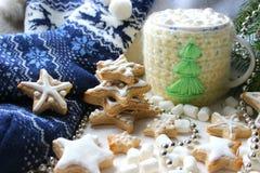 μπλε γυαλί σύνθεσης Χριστουγέννων μπιχλιμπιδιών Καυτό κακάο με marshmallows στο πλεκτό φλυτζάνι, διεσπαρμένα μπισκότα πιπεροριζών στοκ φωτογραφία με δικαίωμα ελεύθερης χρήσης