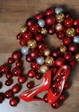 μπλε γυαλί σύνθεσης Χριστουγέννων μπιχλιμπιδιών Κόκκινα λουστραρισμένα με λάκκα παπούτσια με τα τακούνια και ένα στεφάνι των σφαι Στοκ Εικόνες