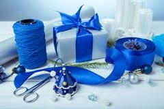μπλε γυαλί σύνθεσης Χριστουγέννων μπιχλιμπιδιών Κώνοι πεύκων, κομψοί κλάδοι, χειροποίητα κεριά, μπλε ντεκόρ Χριστουγέννων σε ένα  Στοκ Εικόνες