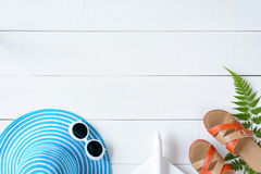 Μπλε γυαλιά ηλίου και παπούτσι καπέλων στον άσπρο ξύλινο πίνακα Στοκ Εικόνες