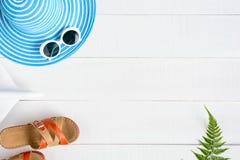 Μπλε γυαλιά ηλίου και παπούτσι καπέλων στον άσπρο ξύλινο πίνακα Στοκ Εικόνα