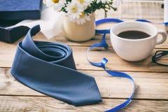 Μπλε δεσμός και ένα ανοιγμένο κιβώτιο δώρων, υπόβαθρο γραφείων γραφείων Στοκ Φωτογραφία