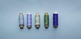 Μπλε εξέλικτρα νημάτων για το ράψιμο σε ένα μπλε υπόβαθρο Έννοια του μπλε, πράσινου ραψίματος, ραπτική, χειροποίητη στοκ εικόνες