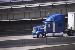 Μπλε ημι φορτηγό εγκαταστάσεων γεώτρησης αστεριών μεγάλο με το ημι ρυμουλκό που τρέχει σε αστικό Στοκ Φωτογραφίες