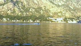 Μπλε θάλασσα, βουνά με τους ανεμόμυλους Νέο ζεύγος που οδηγά το αεριωθούμενο σκι απόθεμα βίντεο